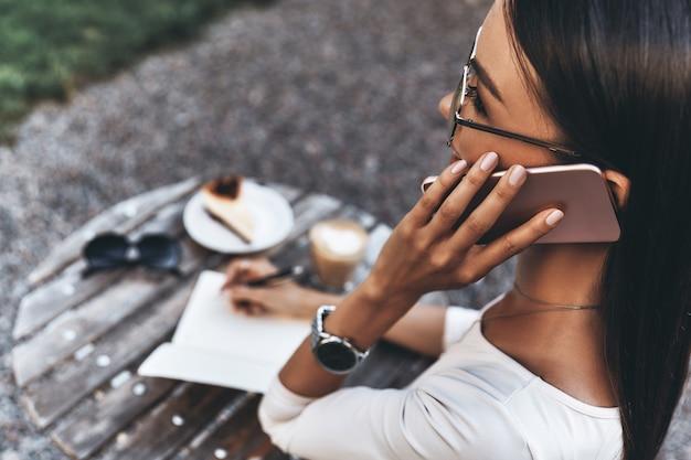 Прислушиваемся к требованиям клиентов. вид сзади привлекательной молодой женщины разговаривает по смартфону и что-то записывает, сидя в ресторане на открытом воздухе