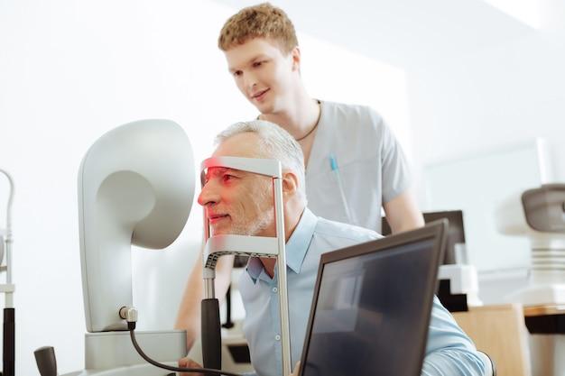 医者の話を聞いています。診察後眼科医の話を聞きながら微笑むイケメン老人