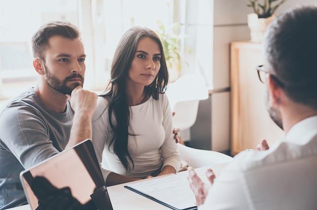 Слушаем финансового консультанта. сосредоточенная молодая пара, связывающаяся друг с другом и слушающая какого-то мужчину, сидящего перед ними за столом в офисе