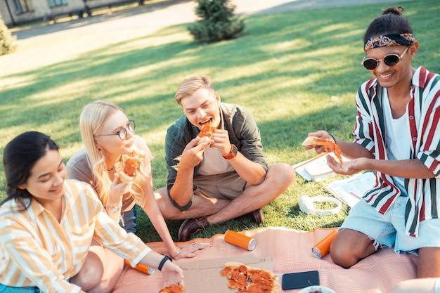 Слушаем друзей. веселые друзья едят пиццу и рассказывают друг другу забавные истории о своих экзаменах во время пикника.