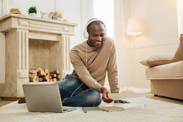 音楽を聴く。彼のラップトップで床に座って、いくつかの論文を見ながら音楽を聴いて魅力的な幸せな笑顔のアフリカ系アメリカ人の男