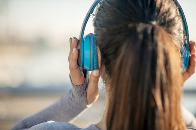 음악을 듣고. 헤드폰에 여자 머리의 클로즈업