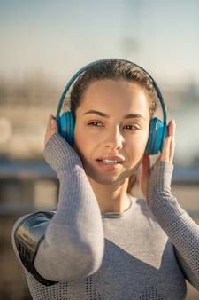 음악을 듣고. 즐거워 보이는 헤드폰을 끼고 있는 소녀의 허리 위로 사진