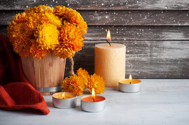 Зажженные свечи аромата и цветы апельсина на деревенском столе.