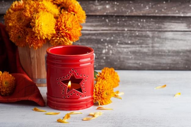 Зажженная ароматическая красная свеча и оранжевые цветы хризантемы на деревенском столе. открытка на праздник