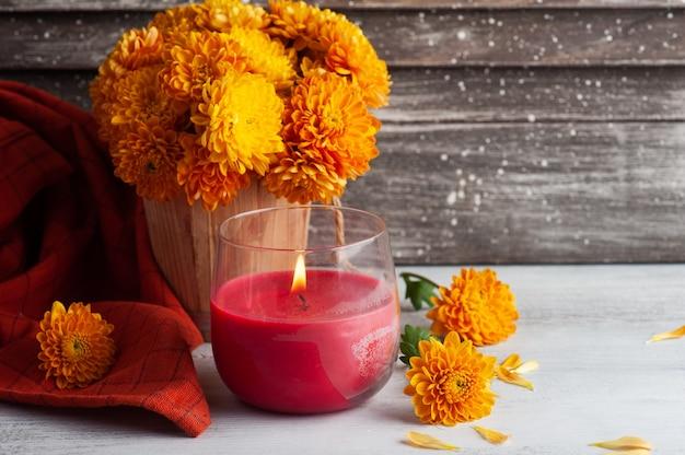 Зажженная ароматическая красная свеча и оранжевые цветы на деревенском столе.