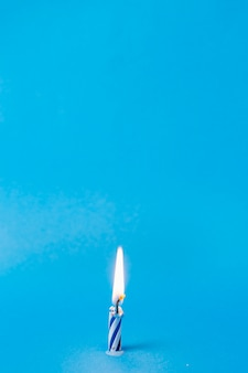 Lit blue birthday candle with copy space
