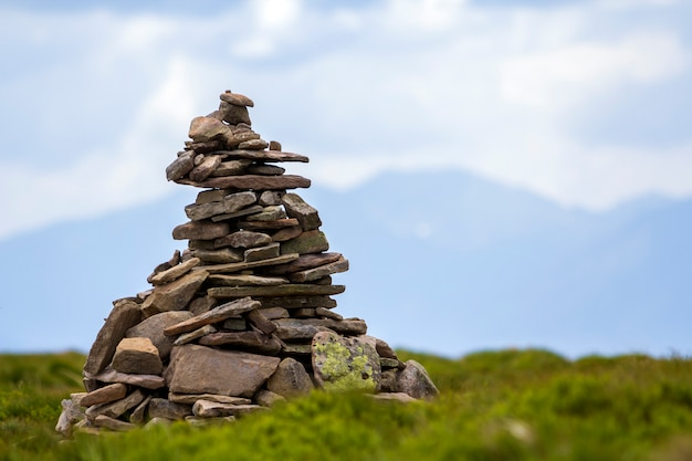 Lit by bright summer sun uneven mountain stones stacked and balanced like pyramid pile on green grassy valley on light white blue copy space sky background. tourism. traveling and landmark concept.