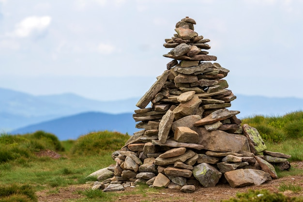Lit by bright summer sun uneven mountain stones stacked and balanced like pyramid pile on green grassy valley on light white blue copy space sky . tourism. traveling and landmark concept.