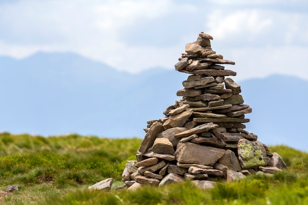 Lit by bright summer sun uneven mountain stones stacked and balanced like pyramid pile on green grassy valley on light white blue copy space sky. tourism. traveling and landmark concept.