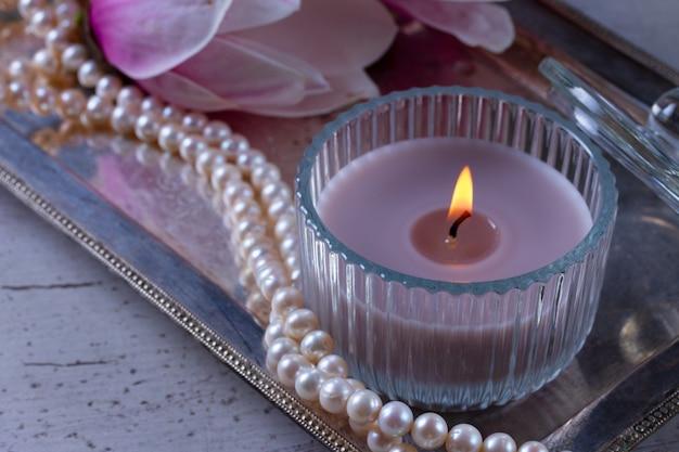 Зажженная свеча и бусы на подносе