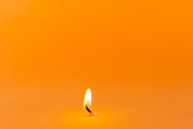 Lit candle on orange background