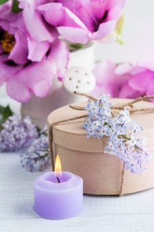 Lit candle, peonies and lilac flowers