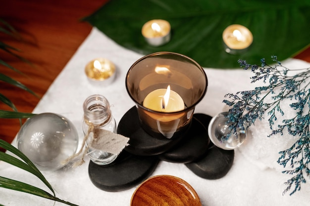 A lit candle standing on stones for a therapy stone with aromatic oil located on a terry towel next to which are transparent spheres, a twisted white terry towel and a sprig of lavender