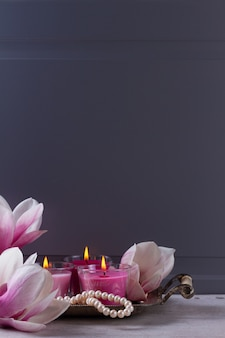Зажженные свечи и бусы на подносе