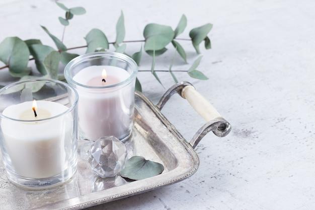 Зажженные свечи и зеленые листья на подносе
