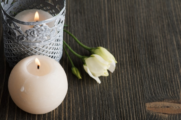 Lit candles and white flowers on dark rustic table