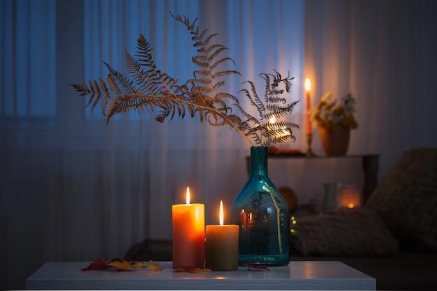 Зажженные свечи с осенним декором на белом столе дома