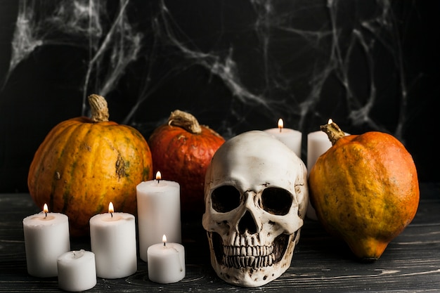 Lit candles with pumpkins and skull