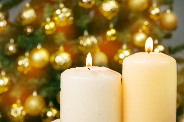 Lit christmas candle against decorated fur tree background