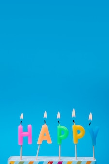 Lit colorful candles with blue background