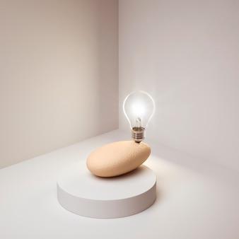 바위에 균형을 잡는 아이디어 개념으로 조명된 전구