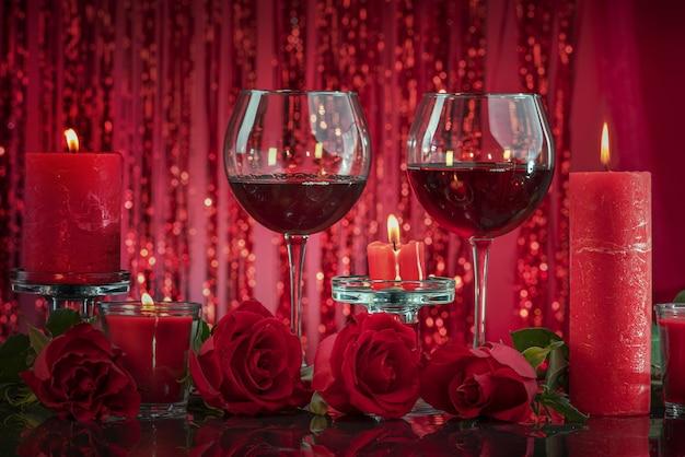 투명한 촛대에 켜진 붉은 양초는 와인을 둘러싸고 있는 안경을 비춥니다.