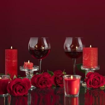 Зажженные красные свечи в прозрачных подсвечниках освещают бокалы с вином в окружении.