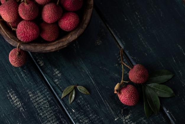 열매는 껍질을 벗기거나 개봉하지 않은 나무 접시에 짙은 나뭇결 테이블 위에 놓습니다.