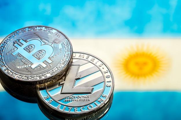 Монеты биткойн и litecoin, на фоне флага аргентины, концепция виртуальных денег, крупным планом. концептуальное изображение.
