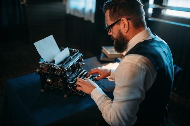 Автор литературы в очках печатает на пишущей машинке