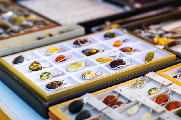 リトアニア。リトアニアの公開市場で販売されているさまざまな色の琥珀色のジュエリー。
