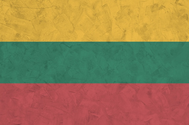 Lithuania flag depicted in bright paint colors on old relief plastering wall. textured banner on rough background