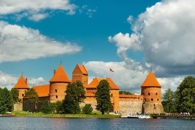 Lithuania. view on trakai castle across lake and white yacht under sail.