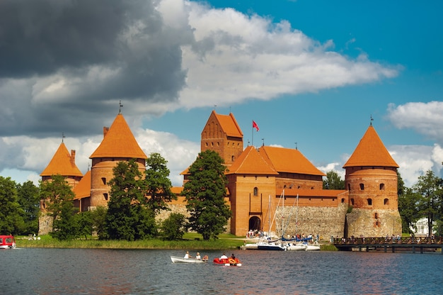 Lithuania. view on trakai castle across lake and white yacht under sail. Premium Photo