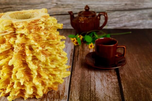 Сакотис литовского торта с чайником и чашкой чая на деревянном столе.