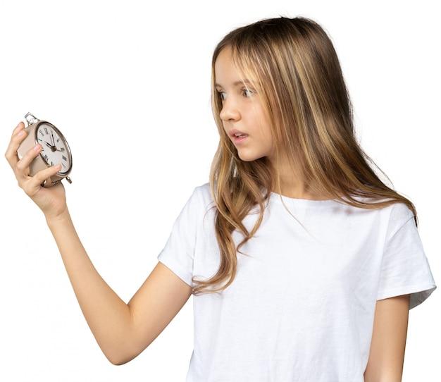 Litle girl with a clock, alarm clock
