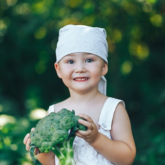 Litle happy smiling farmer boy in white overalls and grey hairband holding fresh organic broccoli in hands