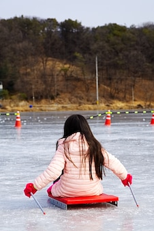 Litle kids riding ice sled ride on the frozen lake