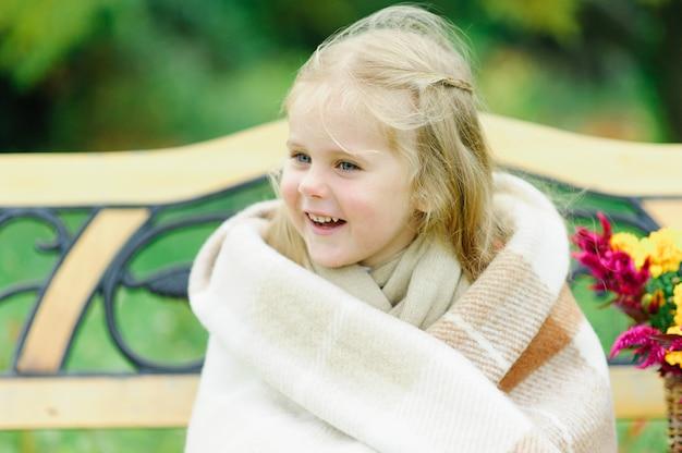 自然の中でベンチに座っているlitlle女の子