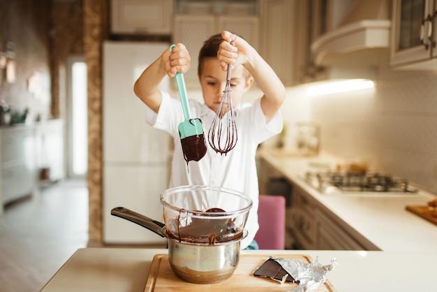 Litte少年はボウルに溶かしたチョコレートをかき混ぜます。キッチンで調理する子供。