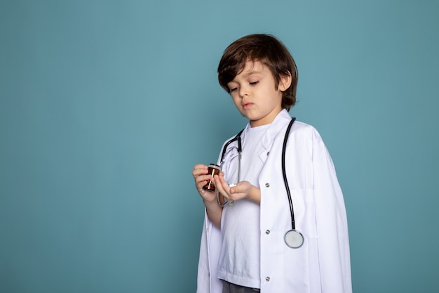 Dolce adorabile sveglio del ragazzo del bambino di litte in vestito medico bianco sulla parete blu