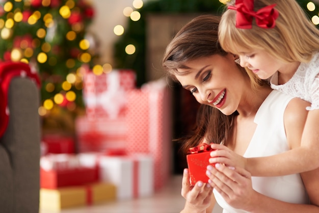 La piccola ragazza sorprende la mamma dando un regalo