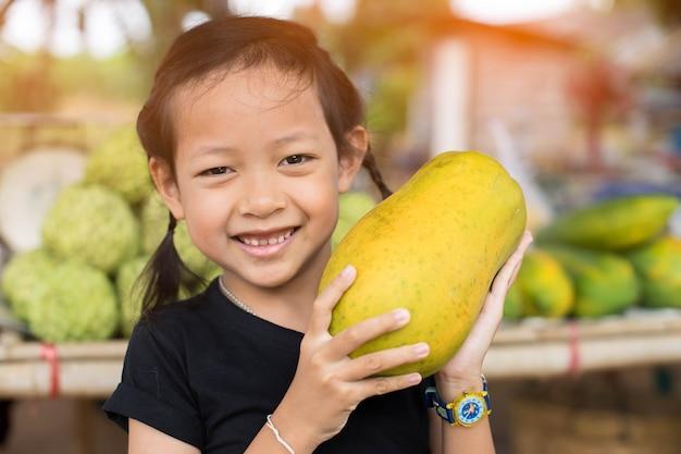 黄色いパパイヤを保持している少し笑っている子女の子。