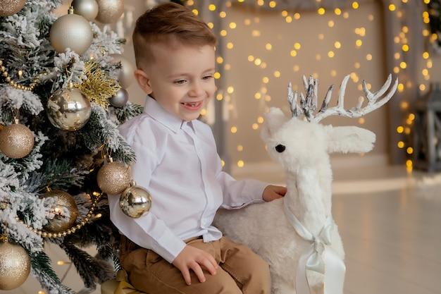 小さな2年の少年は、伝統的なバージョンのスカンジナビアの新年の装飾にクリスマスツリーの美しい代替品をぶら下げつや消しの枝の近くのスタイリッシュな木製クリスマス鹿装飾を抱擁します。