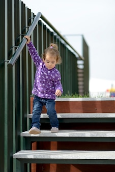Little 20-month-old girl going down some stairs outdoors