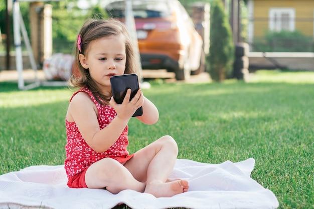빨간 옷을 입은 3-4명의 어린 소녀가 푸른 잔디에 담요에 앉아 스마트폰으로 전화를 겁니다. 가제트를 사용하는 어린이