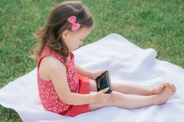 빨간 옷을 입은 3-4명의 어린 소녀가 푸른 잔디에 담요에 앉아 휴대폰을 들여다봅니다. 가제트를 사용하는 어린이