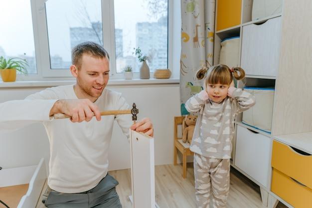 Маленькая 4-летняя девочка закрыла уши руками из-за громкого шума, пока ее отец отремонтировал ящик кровати в детской спальне молотком.