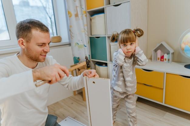父親が子供の寝室のベッドの引き出しを固定するためにハンマーを使用している間、大きな音がするため、4歳の少女は手で耳を閉じます。